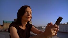 Женщина усмехается пока читающ сообщение на ее мобильном телефоне видеоматериал