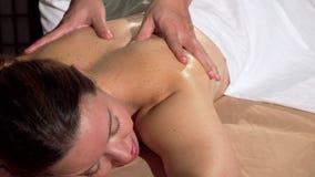Женщина усмехаясь во время ослаблять задний массаж профессиональным masseur сток-видео
