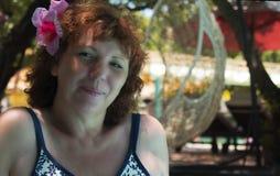 Женщина усмехаясь и привинчивая вверх по ее глазам она в купальнике около бассейна Стоковые Изображения RF