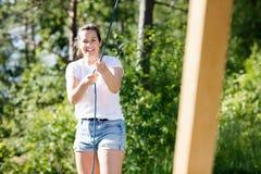 Женщина усмехаясь пока вытягивая веревочка прикрепилась к деревянной структуре Стоковые Фото
