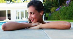 Женщина усмехаясь пока полагающся над бассейном сток-видео