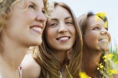 Женщина усмехаясь пока друзья смотря прочь Стоковые Изображения RF