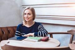 Женщина усмехаясь - портрет счастливой симпатичной и красивой женщины в усаживании вскользь одежд крытом в кафе Стоковое фото RF