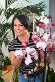 Женщина усмехаясь среди в горшке цветков Стоковые Изображения