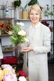 Женщина усмехаясь среди пестротканых цветков Стоковое Фото