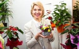 Женщина усмехаясь среди пестротканых цветков Стоковое Изображение