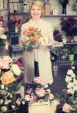 Женщина усмехаясь среди пестротканых цветков Стоковое Изображение RF