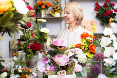Женщина усмехаясь среди пестротканых цветков Стоковые Фото