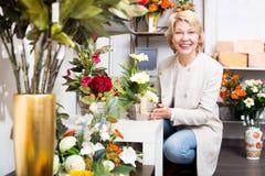 Женщина усмехаясь среди пестротканых цветков Стоковое фото RF