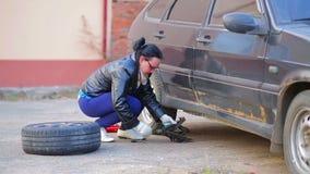 Женщина устанавливает поднимает домкратом для того чтобы поднять автомобиль