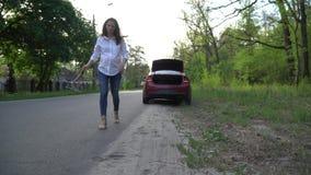 Женщина устанавливает предупреждающий треугольник и вызывает помощь обочины сток-видео
