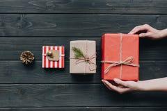 Женщина устанавливая подарок рождества в строке Стоковая Фотография