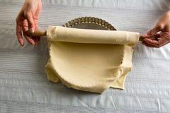 Женщина устанавливая тесто протягиванное над прессформой Стоковая Фотография RF