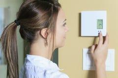 Женщина установила термостат на дом Стоковое фото RF