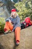 женщина утеса активного backpack взбираясь сидя Стоковое Изображение RF