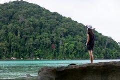 женщина утеса стоящая фронт ее имеет голубое море и зеленый цвет для Стоковые Фотографии RF