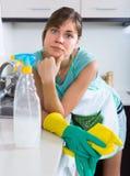 Женщина утомлянная во время уборки на кухне Стоковые Изображения