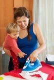 Женщина утюжа с утюгом в комнате Стоковые Фото