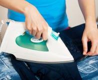 Женщина утюживя ее одежды стоковое изображение rf