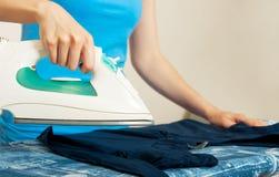 Женщина утюживя ее одежды стоковые изображения rf