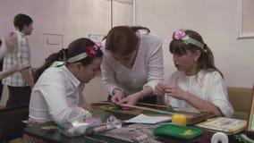 Женщина уча 2 девушкам в оправе цветка как сделать бисероплетение на таблице Handmade хобби творение сток-видео