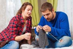 Женщина учит knit молодому человеку стоковые фотографии rf