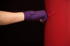 Женщина ударяя сумку бокса, взгляд со стороны стоковое изображение rf