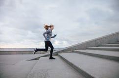 Женщина фитнеса бежать вверх на шагах Стоковое фото RF
