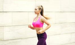 Женщина фитнеса бежать в городе, женской разминке бегуна, спорте и здоровом образе жизни Стоковые Изображения