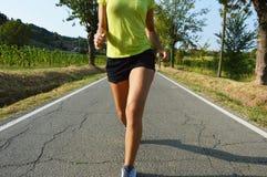 Женщина фитнеса бежать на дороге асфальта стоковое изображение
