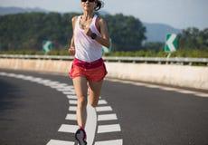 Женщина фитнеса бежать на дороге шоссе стоковое изображение