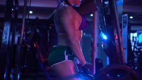 Женщина фитнеса брюнет сильная на спортзале