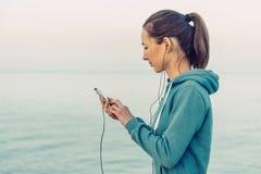 Женщина фитнеса выбирает музыку Стоковые Фотографии RF
