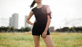 Женщина фитнеса в городском парке принимая пролом от разминки Стоковое фото RF