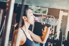 Женщина фитнеса в питьевой воде спортзала просторной квартиры после хорошей разминки Стоковая Фотография