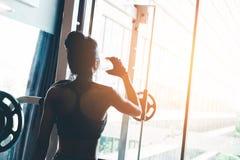 Женщина фитнеса в питьевой воде спортзала просторной квартиры после хорошей разминки Стоковые Фотографии RF