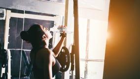 Женщина фитнеса в питьевой воде спортзала просторной квартиры после хорошей разминки Стоковые Фото