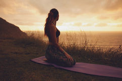 Женщина фитнеса в представлении Vajrasana на заход солнца Стоковая Фотография