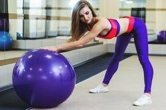 Женщина фитнеса в спортзале отдыхая на шарике pilates Делать молодой женщины Стоковое Фото