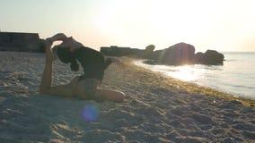 Женщина фитнеса в черном bodysuit и татуировка на ее бедренной кости делая йогу на песке морем или океаном в солнце 4K r видеоматериал