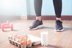 Женщина фитнеса в черных брюках стоя на деревянном поле с гантелями и молочном продучте для разминки Стоковая Фотография