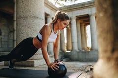 Женщина фитнеса делать нажимает поднимает используя шарик медицины стоковые фотографии rf