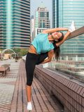 Женщина фитнеса делая повышенные ноги нажим-поднимает на стенде в городе Sporty девушка работая outdoors стоковые фото