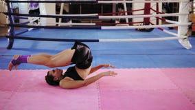 Женщина фитнеса делая подбрюшные хрусты: она поднимает ее ноги вверх после этого двигает их за ее головой внутри боксерского ринг видеоматериал