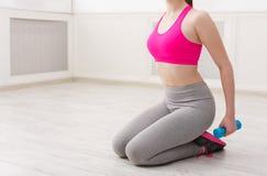 Женщина фитнеса держа гантели на белой предпосылке Стоковое фото RF
