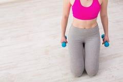Женщина фитнеса держа гантели на белой предпосылке Стоковая Фотография