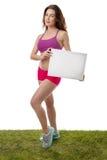 Женщина фитнеса держа пустой знак чистого листа бумаги Стоковые Изображения RF