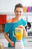 Женщина фитнеса делая smoothie тыквы в кухне стоковое фото