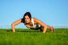 Женщина фитнеса мотивированная делать нажимает поднимает Стоковое фото RF