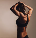 Женщина фитнеса показывая мышечную заднюю часть